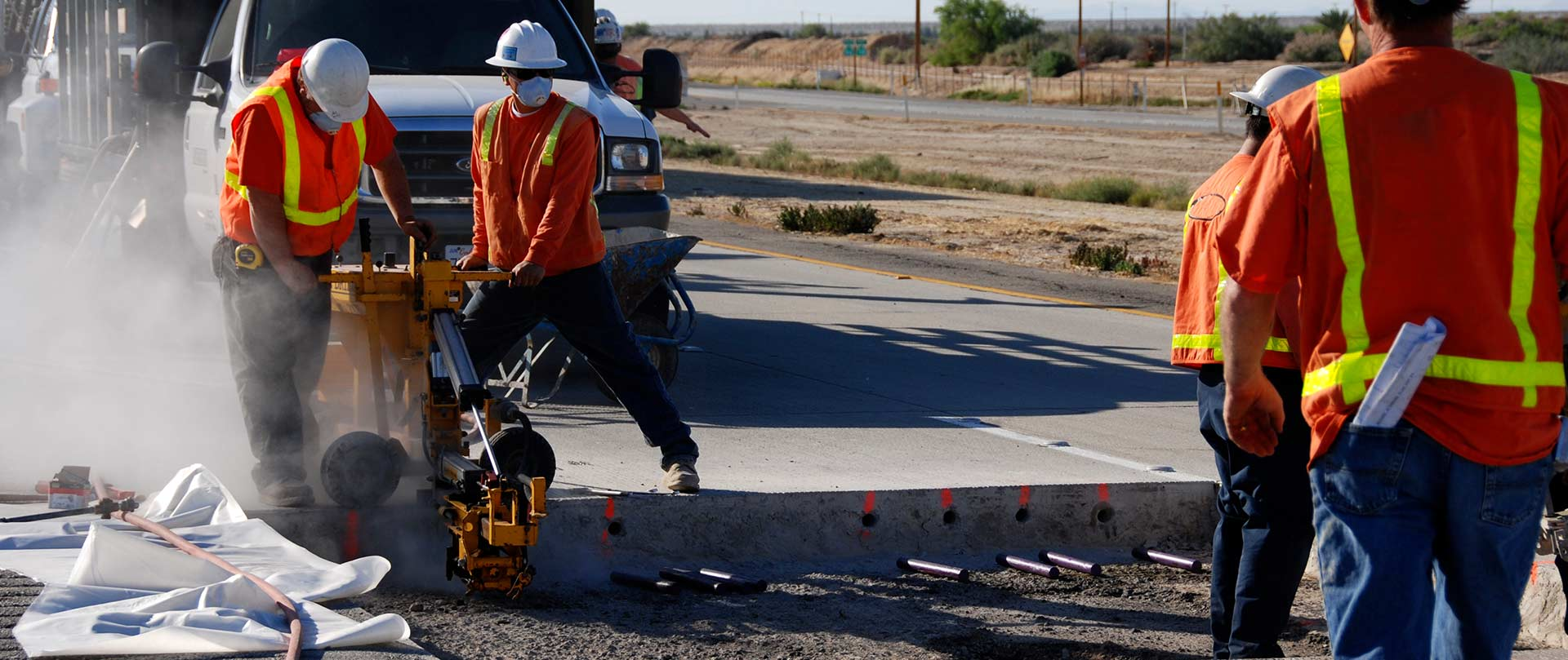 Men practice safety procedures in a road construction zone.