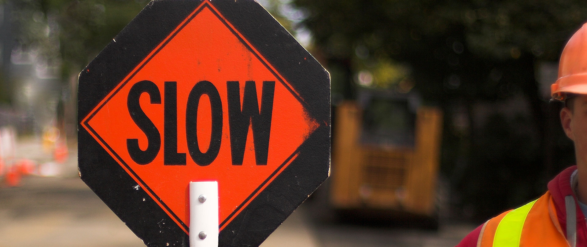 A flagger holds a SLOW sign to direct traffic and increase work zone safety.